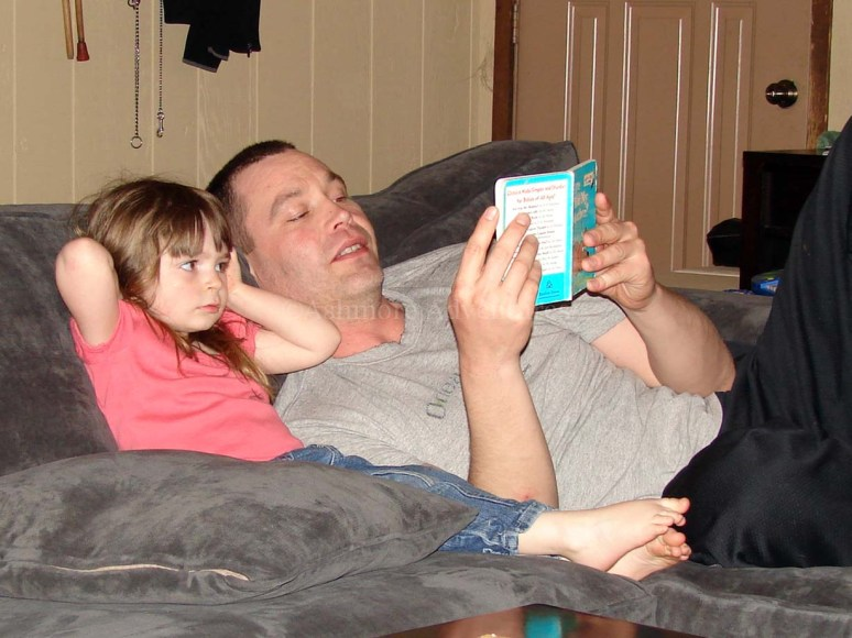 4/8/13 Reading with Uncle Ryan...not sure why she has her hands over her ears.
