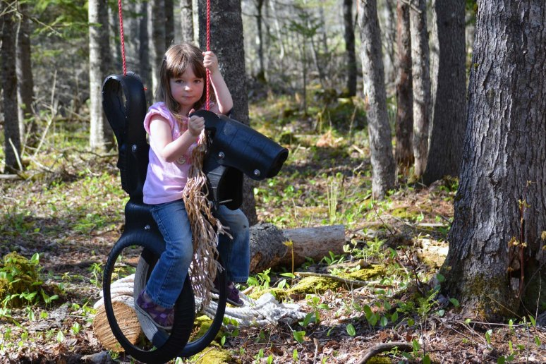 "5/10/13 Riding ""Ted"", her horse swing that Nanny gave her for Christmas."